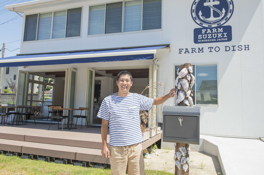 Takashi Suzuki standing in front of the Farm Suzuki restaurant located inside his oyster farm.