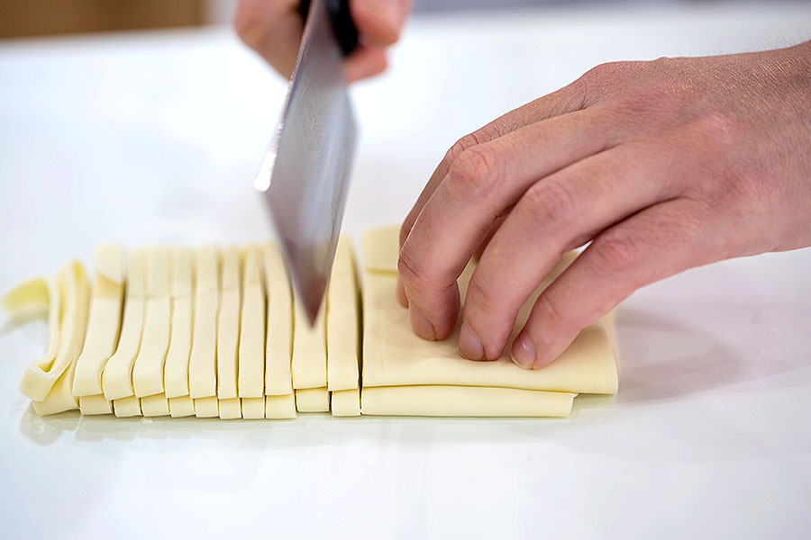 After vigorously kneading and trampling on the dough, students carefully cut it into the flat rectangular shape characteristic of Sanuki udon variety.