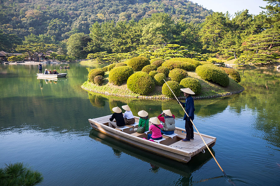 Passengers aboard a wasen (small wooden boat) take a tour of the grounds via the calm waters of the Nanko or South Pond.