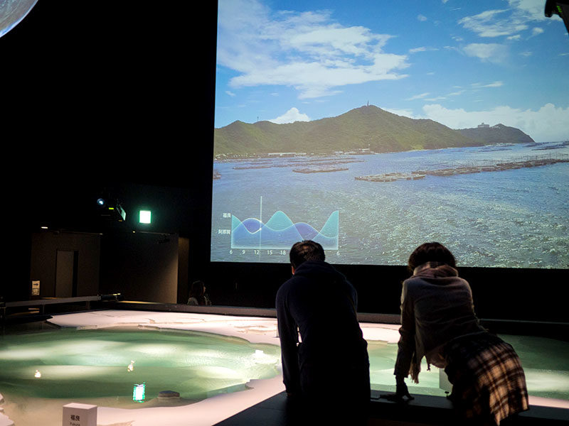 Visitors inside the movie theatre take a closer look at the scale representation of the Naruto bridge and whirlpools.