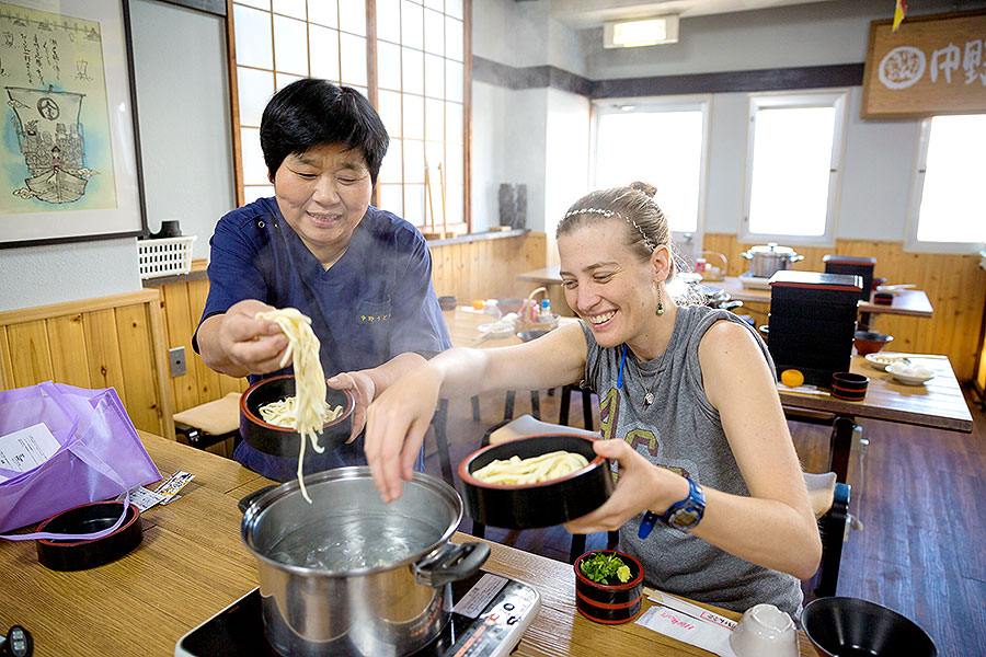 Instructor Ma-chan helps add the noodles to the boiling water.