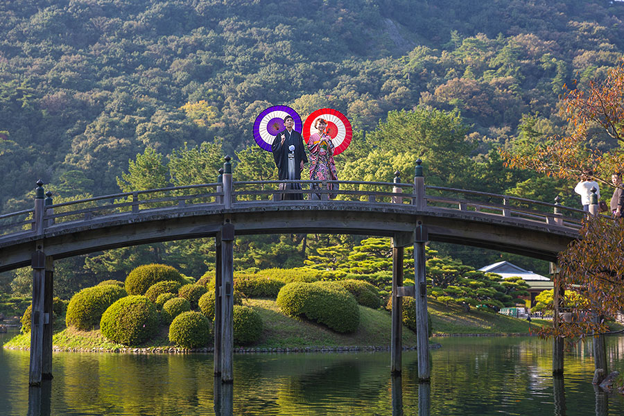 Two young newlyweds in full traditional Japanese marriage regalia pose on the crescent-shaped bridge to make a memory that will last a lifetime.