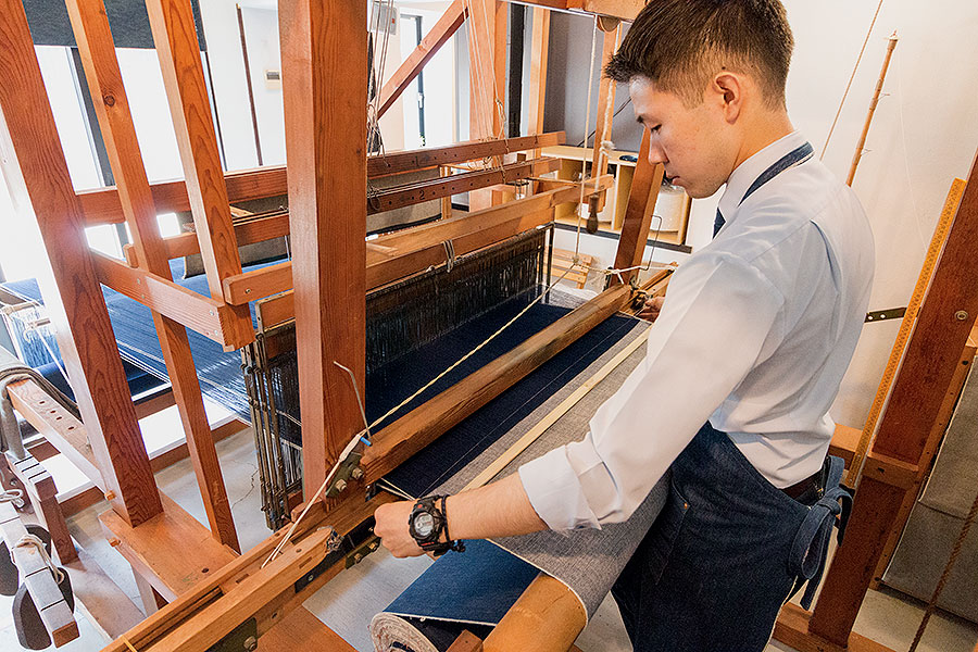 A craftsman at Momotaro Jeans weaving denim on a classic, hand-operated loom.