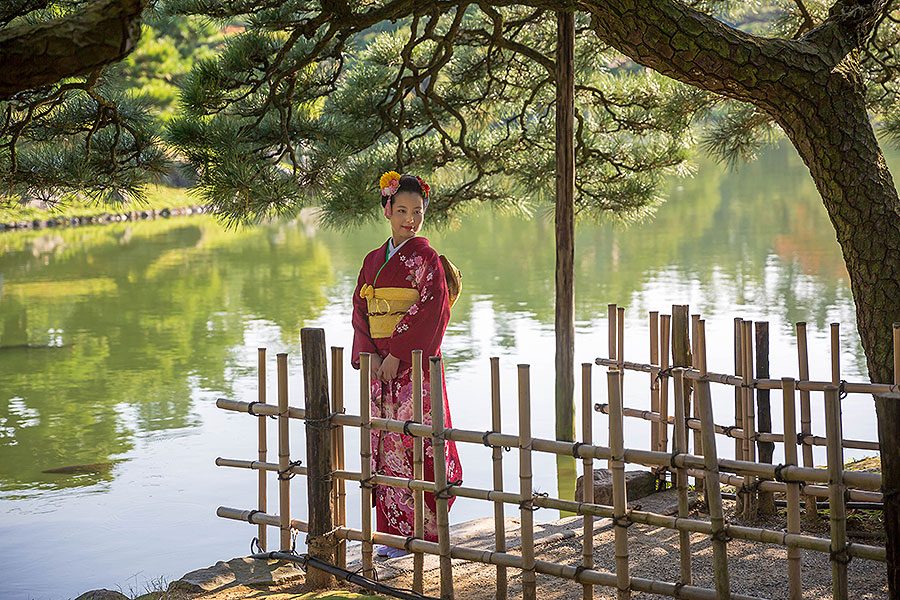 A beautiful young woman in a kimono pauses in an alcove off the main path.