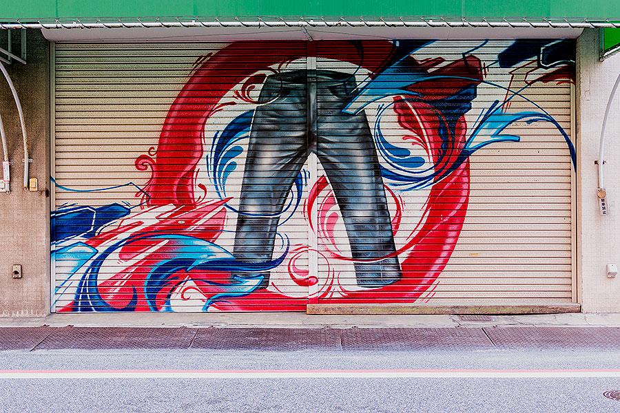 A mural graces a former storefront shutter above indigo blue asphalt on Kojima Jeans St.