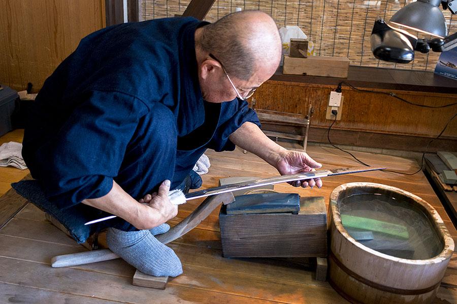 Takayama Toshio, sword polisher and sharpener, works the blade of a hand forged katana at Bizen Osafune Sword Museum.