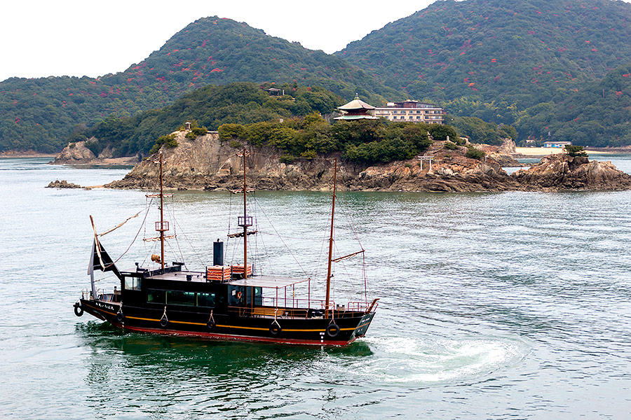 Tomonoura's local island-hopping ferryboat, styled after a historical pirate ship, makes regular rounds to and from a dock hard by.