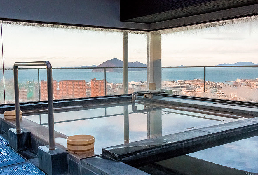 Luxuriate in an onsen bath against a backdrop of urban and natural beauty.