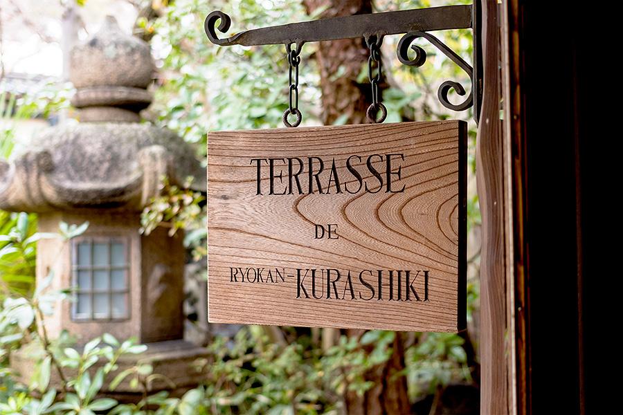 The handmade wooden sign hanging outside Terrasse, Ryokan Kurashiki's vintage lounge.