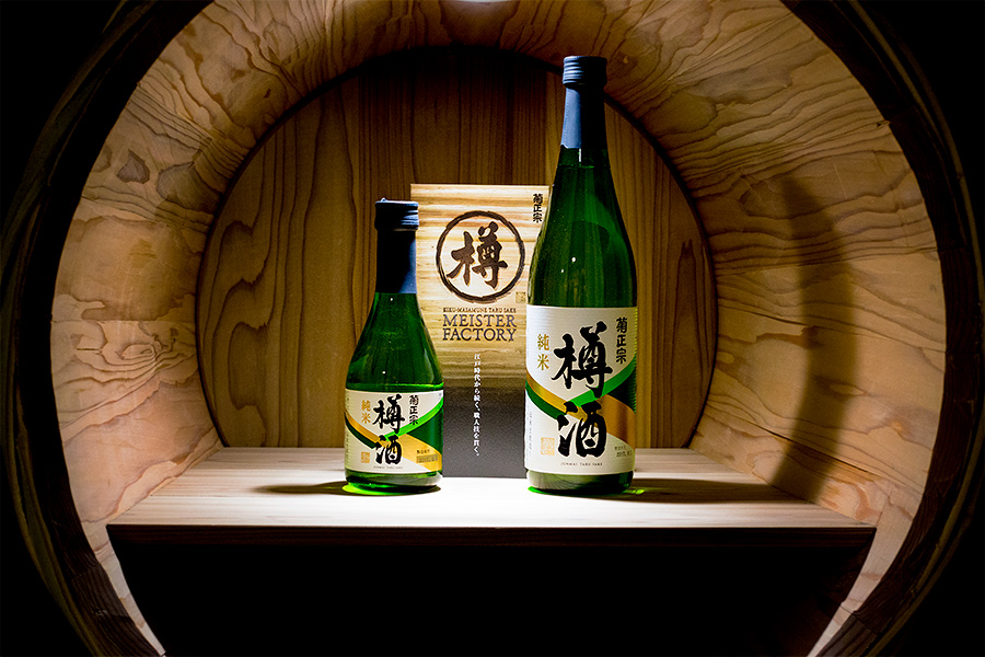 Some Kiku-Masamune's top-shelf offerings displayed in one of the handmade sake barrels which they construct using traditional craftsmanship onsite in their Kobe facility.