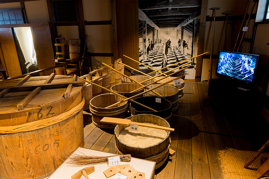 A display at Kiku-Masamune shows one of the most important parts of the sake brewing process — stirring the rice, koji (sake spores), and water with bamboo poles, during which workers sing special songs to keep time and measure their progress.