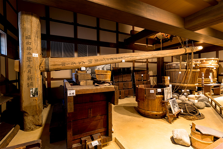 Using a long wooden lever and stone weights like this one on display at Kiku-Masamune, brewers in former times compressed the moromi (raw sake) to separate out the sake lees.
