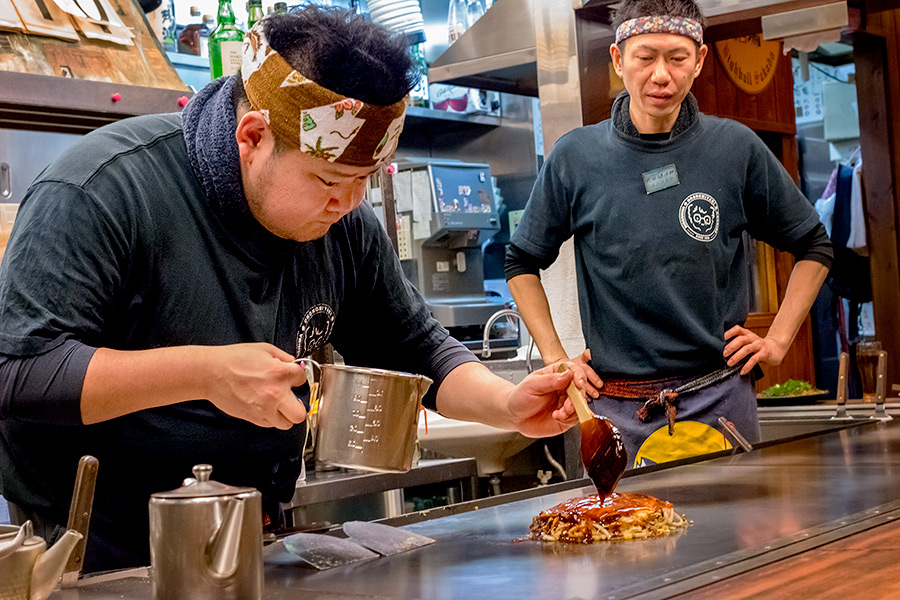 With a practiced hand, Naoki Shimoji applies the special sauce which forms the foundation of okonomiyaki.