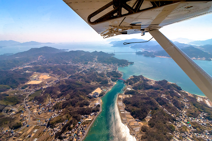 Flying at a mere 700 meters, fine details such as boats plying the waves, houses nestled among the hills, and cars driving down the roadways remain visible to the eye.